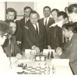 """Από το αρχείο του Μενέλαου Ταφτσόγλου.Από αγώνα του Ομίλου Σκακιστών Ηλιούπολης με τον ΑΜΟ Γαλαξία. Στην πρώτη σκακιέρα του ΟΣΗ αγωνίζεται (δεξιά) ο Τσέντος Χατζηχρήστος, παλιός ποδοσφαιριστής του ΠΑΟΚ, που αργότερα διετέλεσε και προπονητής του Ορφέα Ηλιούπολης στο ποδόσφαιρο. Την έναρξη των αγώνων κάνει ο Πρόεδρος της ΕΣΘ Καρασάββας ενώ παρακολουθούν οι Μενέλαος Ταφτσόγλου, Αντώνης Δούκας, Απόστολος Σαρόγλου,Οδυσσέας Κυριακίδης, ο δημοσιογράφος της σκακιστικής στήλης της εφημερίδας """"Θεσσαλονίκη"""" Δημήτριος Σειρηνόπουλος κ.ά."""