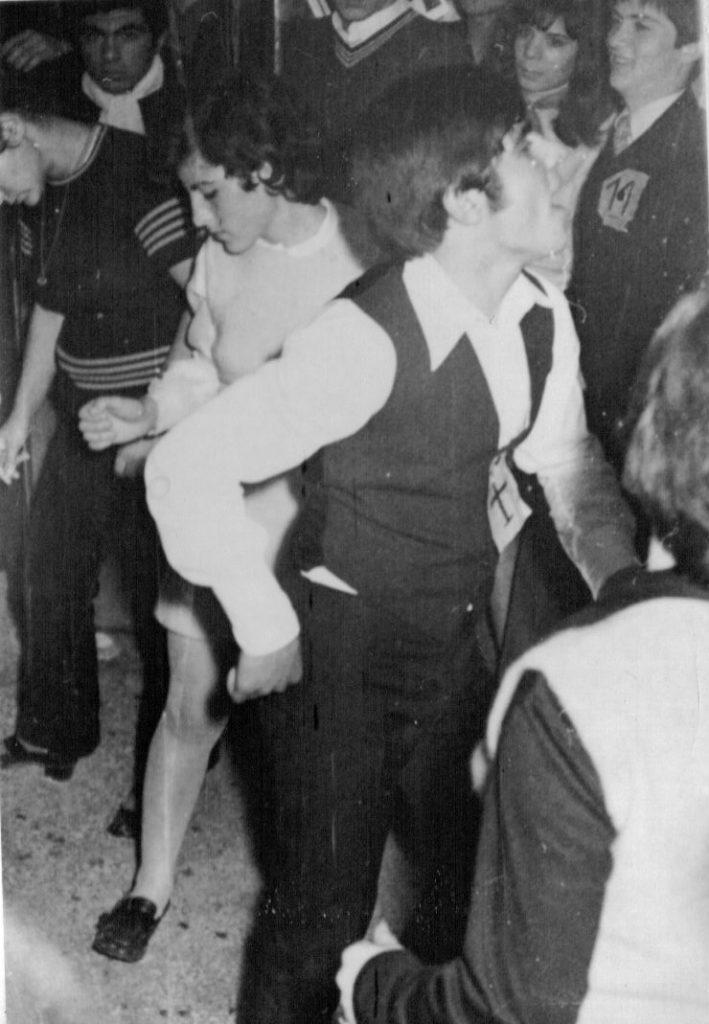 """1969 - Από πάρτι εκείνης της εποχής.  Στα πέτα καρφιτσωμένοι αριθμοί για το διαγωνισμό χορού. Με το Νο11 στο βάθος ο Τέλης Σταθούδης .Με το Νο7 και με το """"χίππικο"""" χορευτικό σκέρτσο ο Βασίλης Τσιβελεκίδης."""
