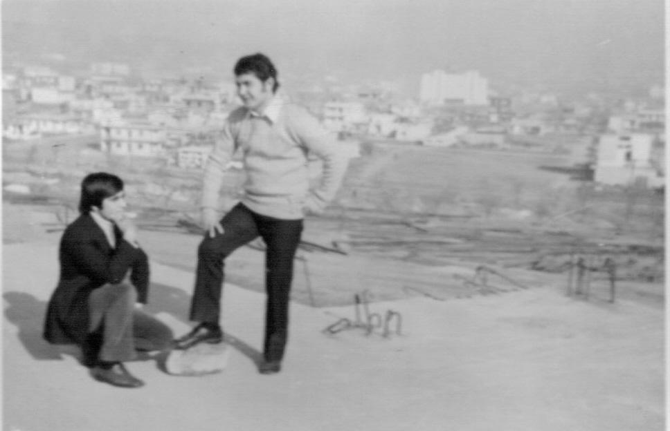 1969 - Βασίλης Τσιβελεκίδης - Τάκης Σταμπουλής.  Στη ταράτσα του ημιτελούς σπιτιού που υπήρχε για πολλά χρόνια  επάνω στα χωράφια. Λίγο πιο πίσω από το σημερινό γήπεδο ποδοσφαίρου του Γ.Σ.Ηλιούπολης.Πίσω φαίνονται τα πρώτα σπίτια της Άνω Ηλιούπολης.