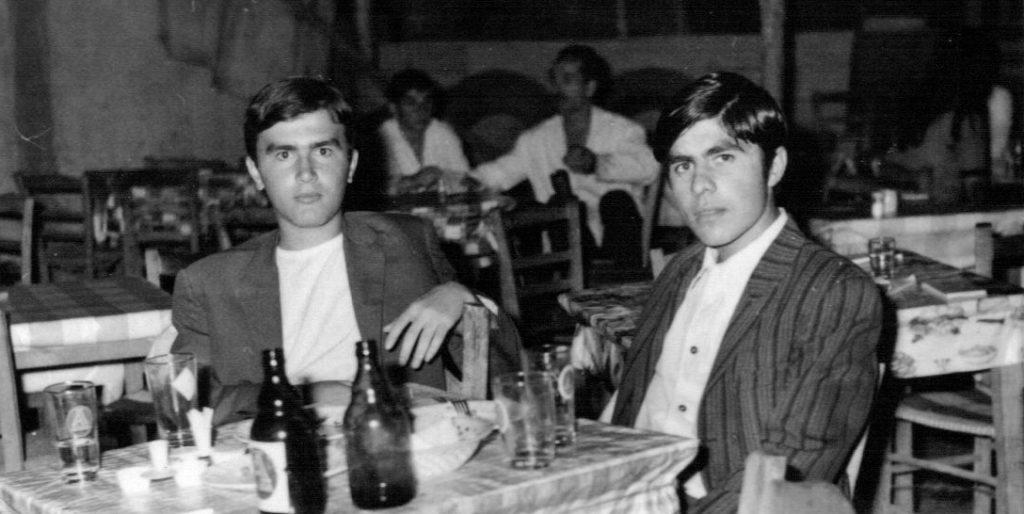 """1970 - Παύλος Αντωνιάδης - Βασίλης Τσιβελεκίδης  Στη ταβέρνα του """"φαλάκρα"""" (δίπλα στο φωτο-Κυριακίδη).Πίσω διακρίνεται ο γνωστός σερβιτόρος Γιώργης."""